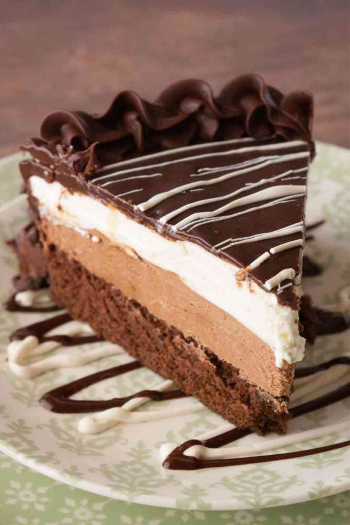 Black Tie Mousse Cake slice drizzled with white chocolate.
