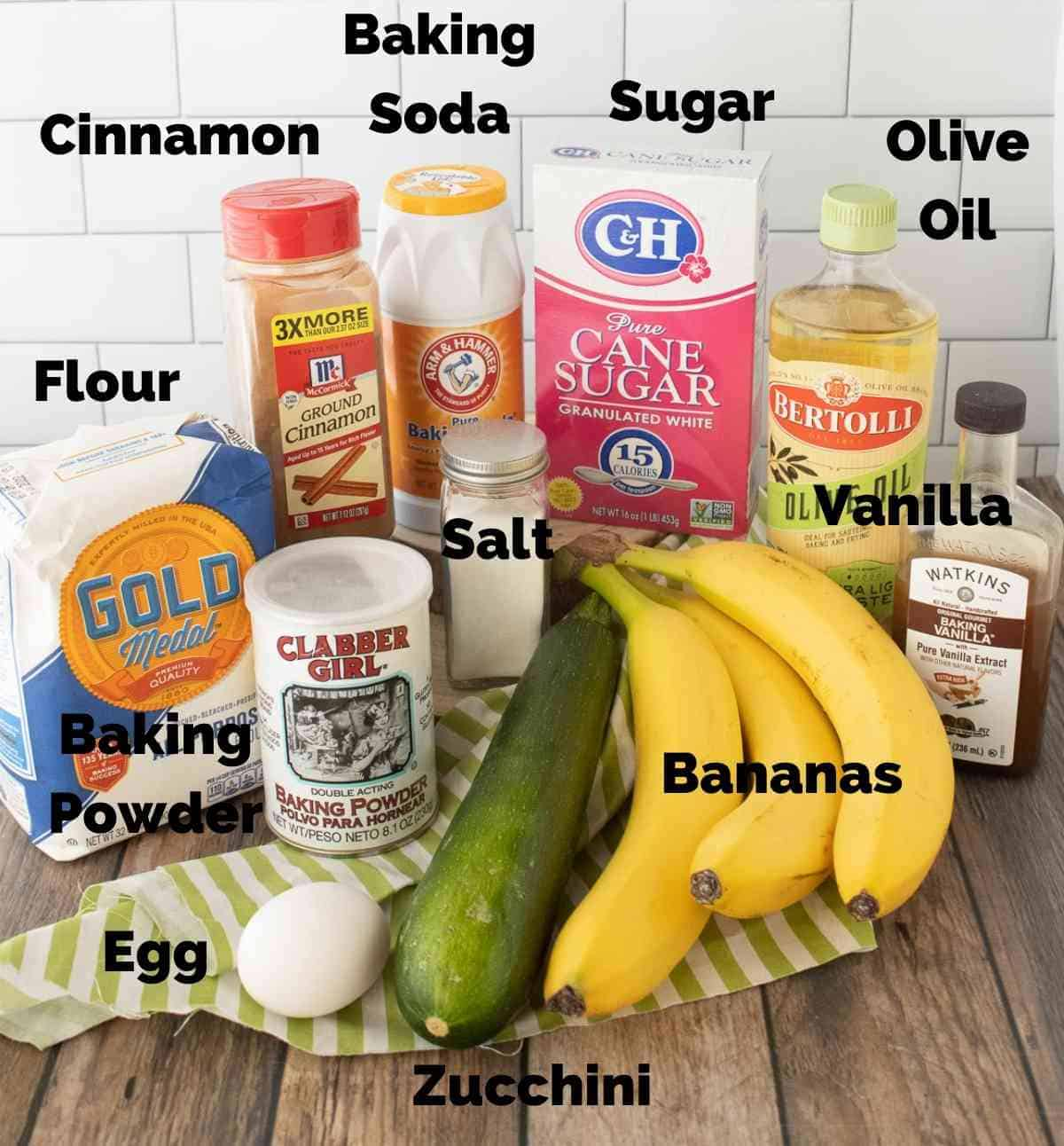 Ingredients needed for this recipe are Flour, Sugar, Cinnamon, Baking Soda, Baking Powder, Olive Oil, Salt, Vanilla, Bananas, Zucchini, and an Egg.