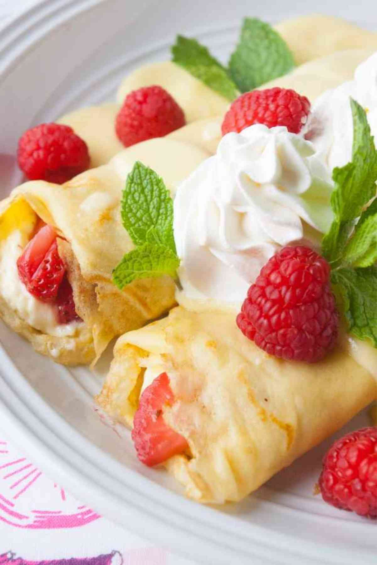 Two berry cream filled crepes garnished with raspberries and mint!