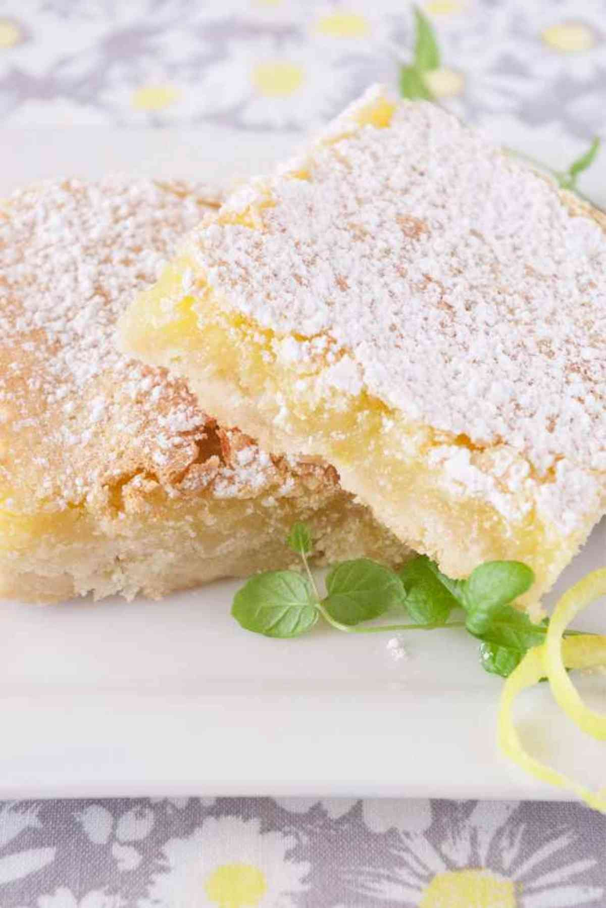 Two lemon bars on a plate garnished with mint.