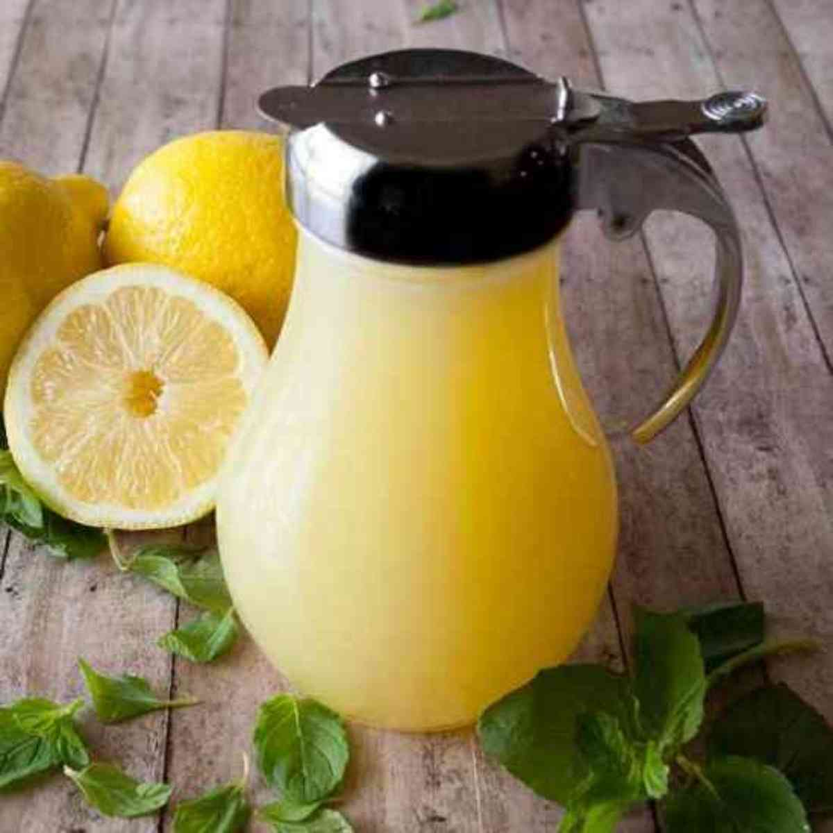 Lemon Cream Syrup next to fresh lemons and mint.