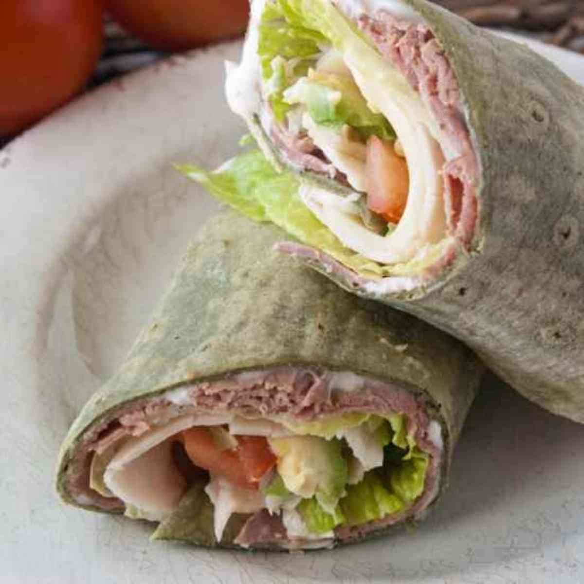 Roast beef turkey wrap cut in half and put on a plate.