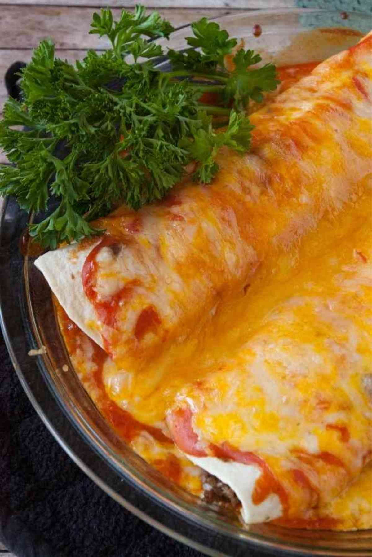 A plate of two ground beef enchiladas.