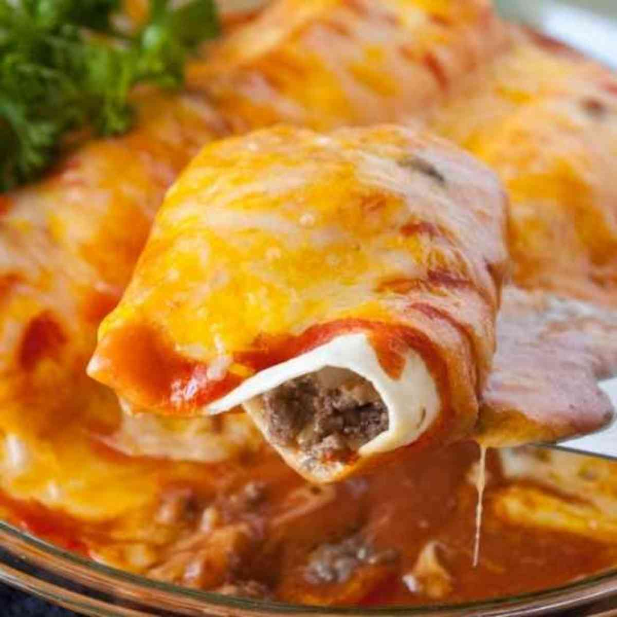 A fork lifting a bite of ground beef enchiladas.