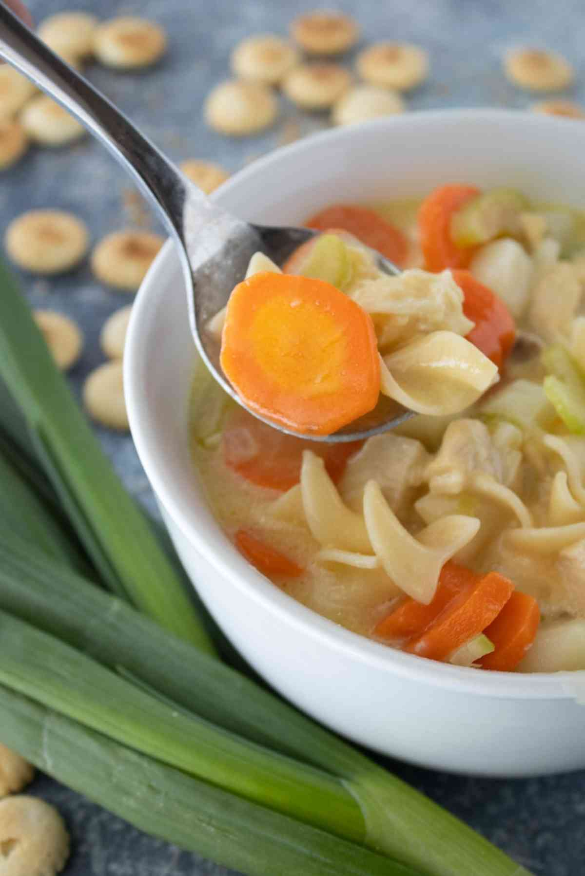 A spoonful of creamy chicken noodle soup being lifted out of the bowl.