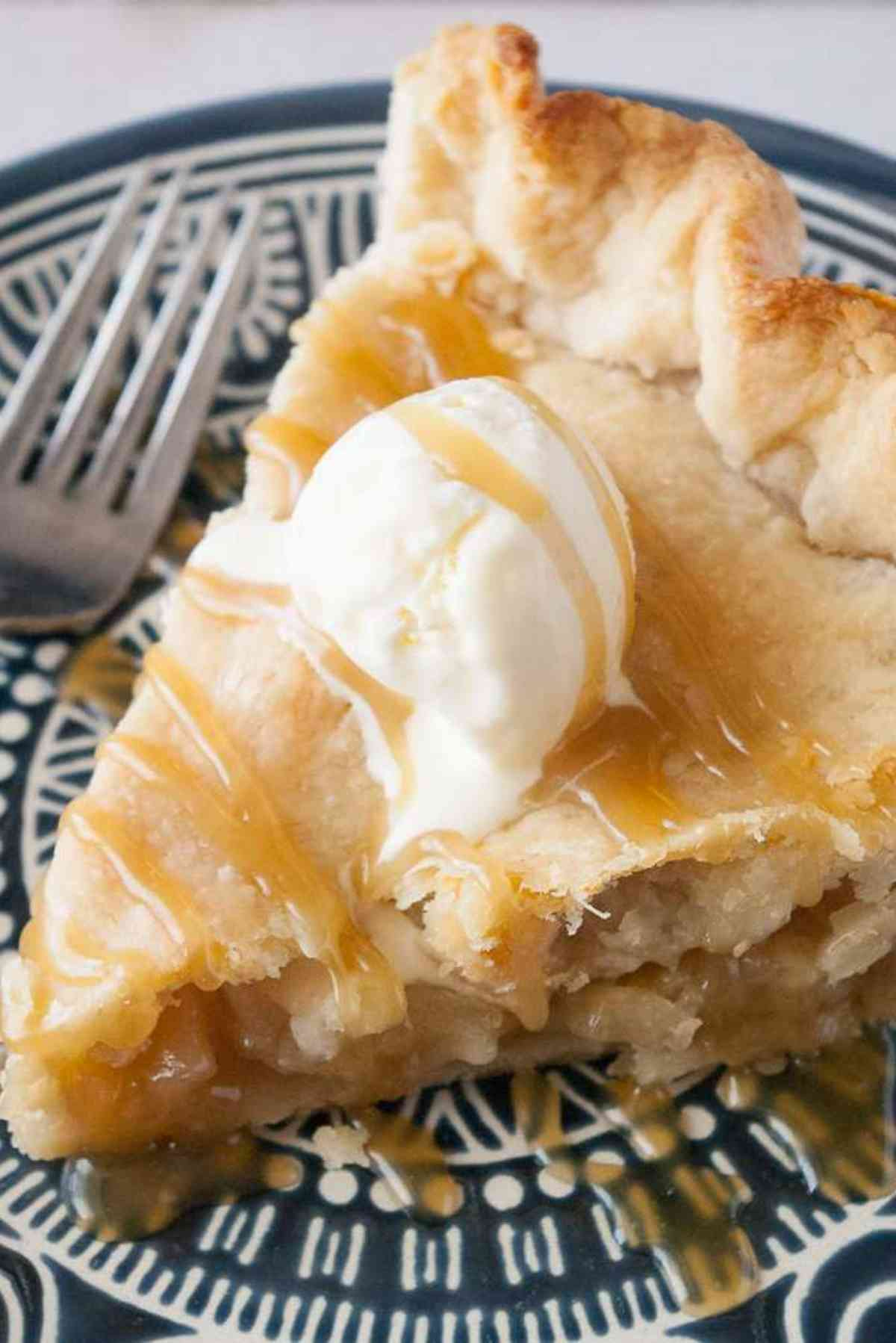 Big slice of the best caramel apple pie with a scoop of vanilla ice cream on top drizzled with extra caramel.
