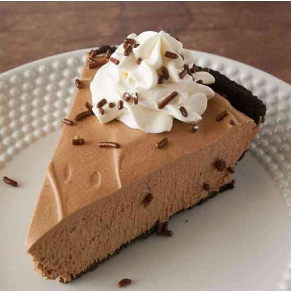 Slice of chocolate mousse pie garnished with whipped cream.