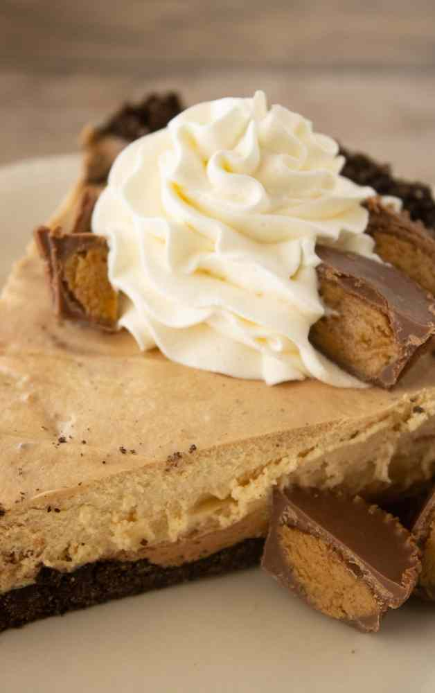 A slice of chocolate peanut butter mousse pie topped with whipped cream and chopped up reese's peanut butter cups.