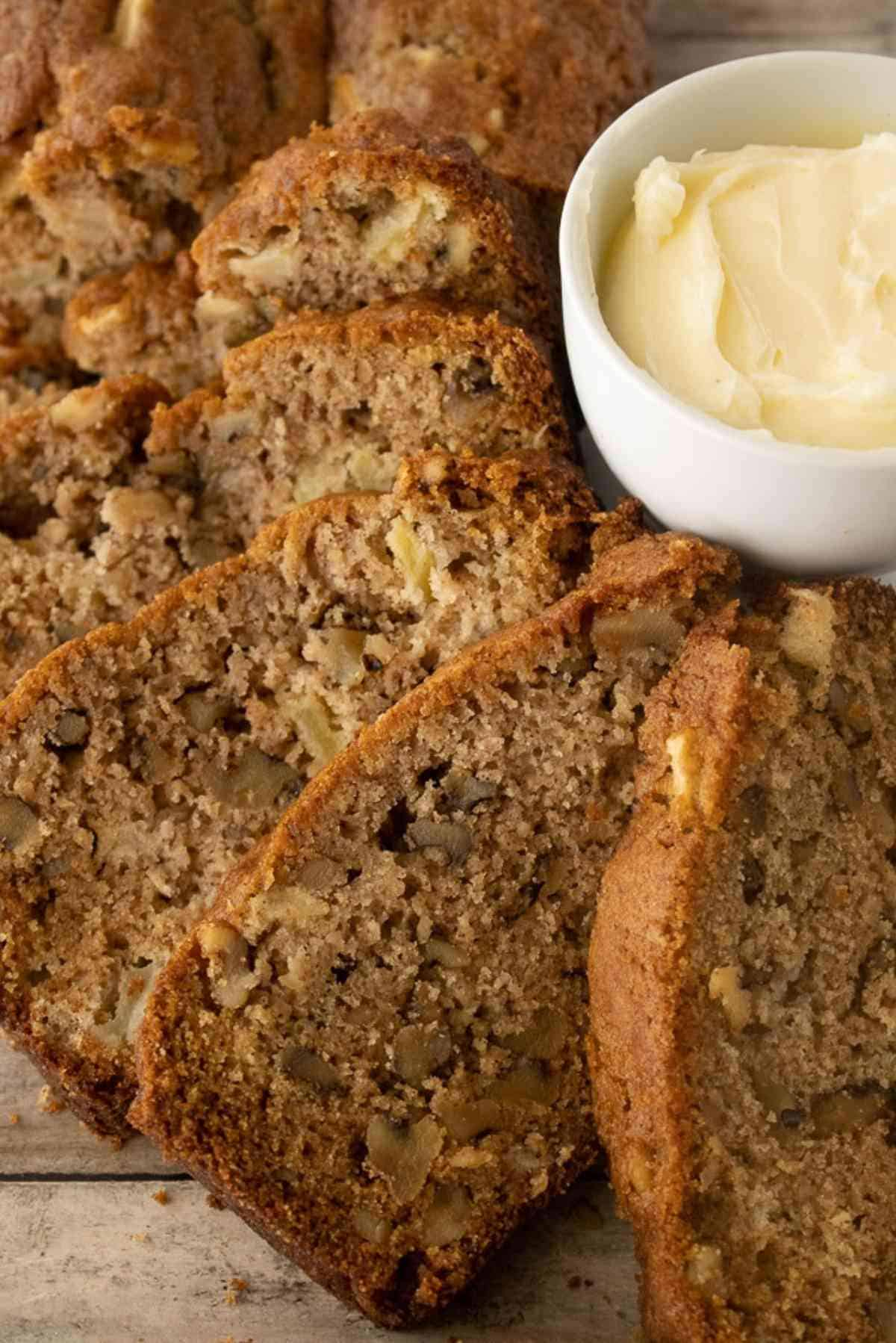 Slices of walnut apple bread arranged around a butter dish.