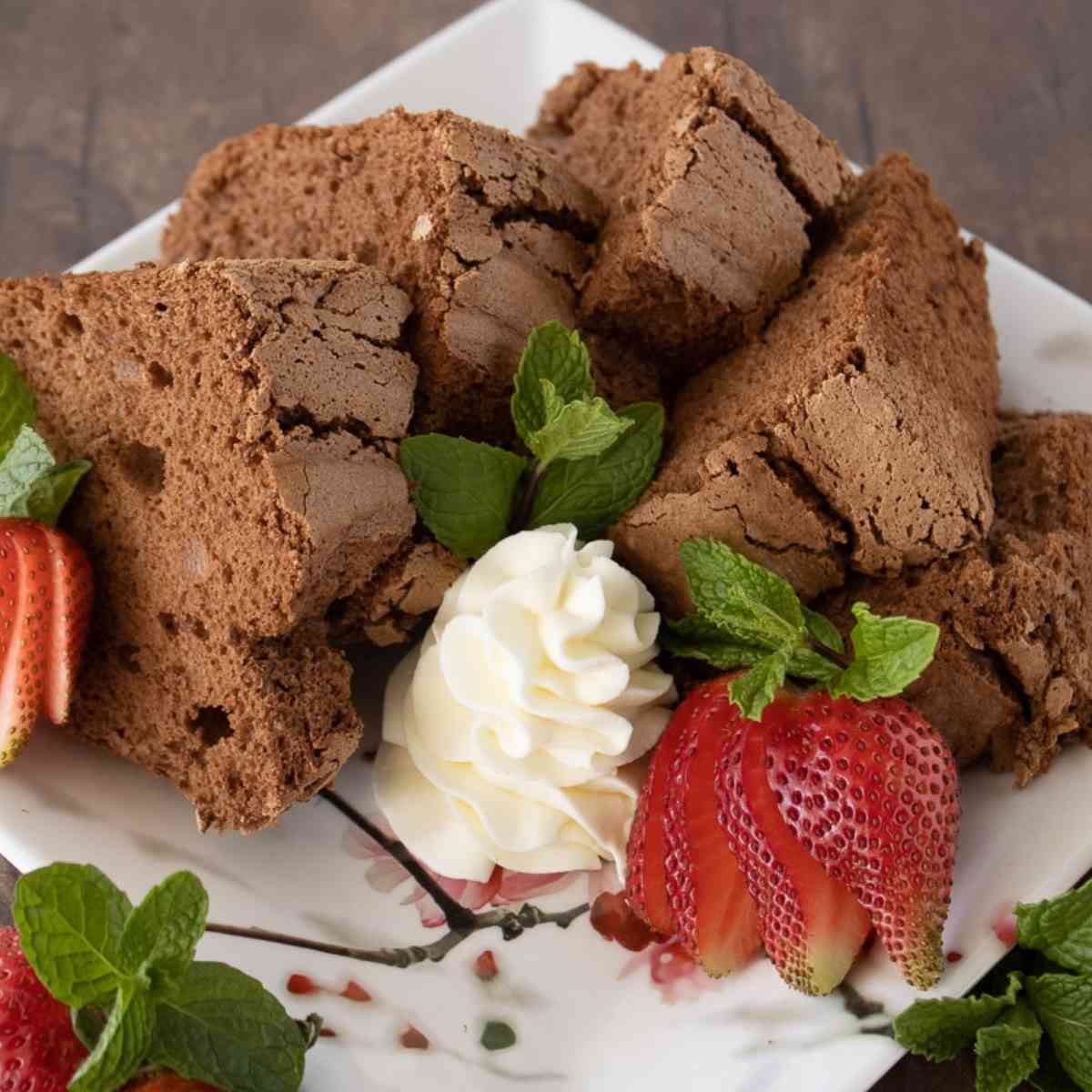 Plate of chocolate angel food cake wedges with strawberries.